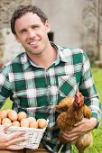 Young man holding his chicken and basket of eggs in his garden smiling at camera
