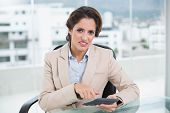 Annoyed businesswoman using calculator in bright office