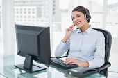 Joyful classy brown haired operator answering a call in bright office