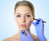 Beautiful woman ready for cosmetic surgery, female face with doctor's hands drawing lines on skin, o