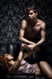 stock photo of leather-bound  - Young couple in bdsm action on the leather sofa - JPG