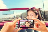 stock photo of two women taking cell phone  - Taking pictures with smart phone of woman in car - JPG