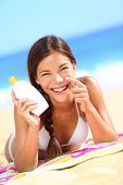 stock photo of suntanning  - Suntan lotion woman applying sunscreen solar cream laughing having fun - JPG