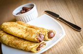 stock photo of crepes  - Golden homemade crepes with dark chocolate cream - JPG