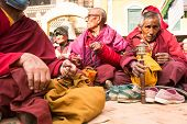KHATMANDU, NEPAL - DEC 17, 2013: Unidentified Buddhist pilgrims near stupa Boudhanath during festive