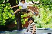 Cheerful kids having fun jumping on trampoline