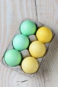 High angle shot of a six pack of Easter eggs on a rustic kitchen table. Vertical format.