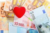 Cost Of Health Care: Red Heart Syringe On Euro Money