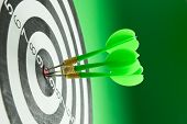 picture of throw up  - Three green darts pinned right on the center of dartboard - JPG