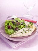 mackerel fillet with salad and slice grapes over lilac table