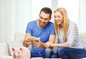 love, family, finance, money and happiness concpet - smiling couple counting money with piggybank ot table at home