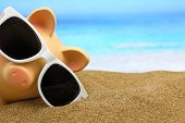 stock photo of piggy  - Summer piggy bank with sunglasses on the beach - JPG
