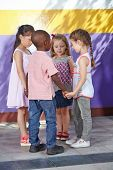 Four children dancing in circle in a kindergarten class
