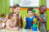 Children with nursery teacher building tower in a kindergarten group