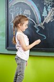 Girl drawing a picture on a bloackboard with chalk in the kindergarten