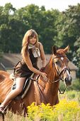 Beautiful Teenager Girl Riding Horse At The Field Of Flowers
