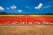stock photo of track field  - Running track over blue sky and clouds - JPG