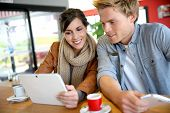 Young couple in coffee shop websurfing with tablet