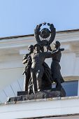 Figures of the Soviet soldier, worker and peasant on the roof of the building