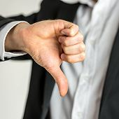 stock photo of disapproval  - Man giving a thumbs down gesture of disapproval showing his negativity and dissatisfaction close up of his hand - JPG