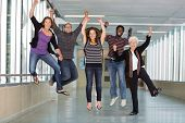 Full length portrait of excited multiethnic university students jumping in corridor with professor
