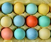 Closeup of an Easter Egg Carton on a rustic farmhouse kitchen table. The carton is lined with yellow