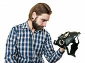 stock photo of rubber mask  - the man with a beard watching at a gas mask it is isolated on a white background - JPG