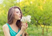 beautiful happy smiling girl with long dandelions in the hands of shorts and a t-shirt is resting
