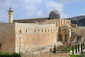 The ancient walls of Jerusalem, lit morning sun. Gray dome of the Al-Aqsa Mosque on the Temple Mount in Jerusalem