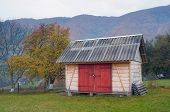 Country yard with wooden shed. Autumn in mountain village
