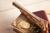 colt revolver and gold coins