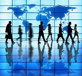Side View Photo Of Silhouettes Of Business People Walking Indoors And Cartography Of The World Above