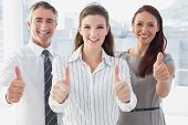 Smiling businesswoman giving thumbs up with co-workers