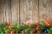 Christmas tree branch with lights on grunge wood background
