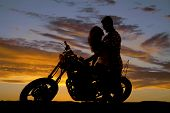 picture of she-male  - A man looking down at his woman as she sits on a motorbike looking into her eyes - JPG