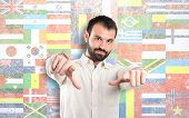 Young Man Pointing Opposite Over Flags Background