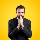 Young Businessman Pleading Over Yellow Background