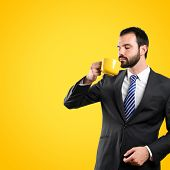 Young Businessman Drinking A Coffee Over Yellow Background