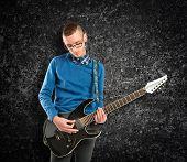 Young Man Playing Guitar Over Black Background