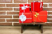 Christmas presents on stool on brown brick wall background