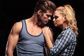 Hot blonde woman holding her hands on her boyfriend shoulder, both looking away. On studio backgroun