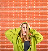 Young Girl Doing Surprise Gesture Over Bricks Background