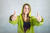 Pretty Young Girl With Thumbs Up Over Textured Background