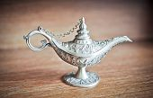 Ancient Aladdin's magic lamp. Silver Genie lamp on wooden table. Old style oil lamp