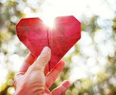 foto of sweethearts  - a hand holding an origami paper heart up to the sun during sunset - JPG
