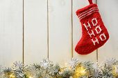 Fir branch with Christmas lights and Santa's red stocking on wood background