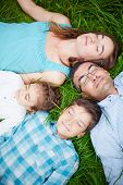 Serene family of four relaxing on grass with closed eyes