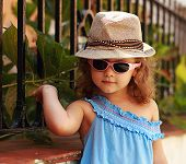 Fashion Small Kid In Glasses And Hat Posing Near The Fence Outdoors Background