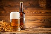 Glass and bottle of beer with wheat ears on wooden planks