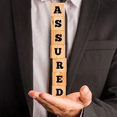 Businessman Holding Letter Blocks Spelling Assured